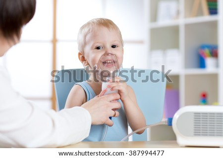 Child with asthma problems making inhalation with mask on her face - stock photo