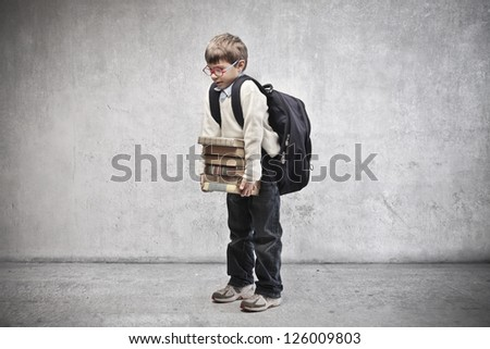 Child with backpack holding some school books - stock photo