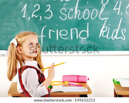 Child with backpack writting text on blackboard. - stock photo