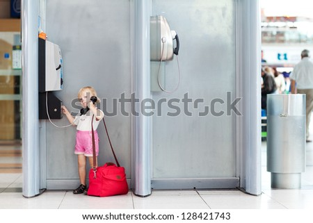 child with bag talking the phone in the airport - stock photo