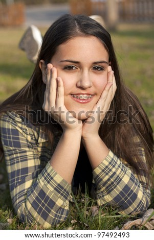 Child with braces smiling in a field - stock photo