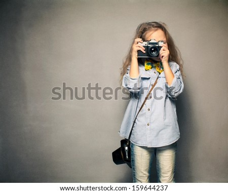Child with camera. Little girl photographing - stock photo