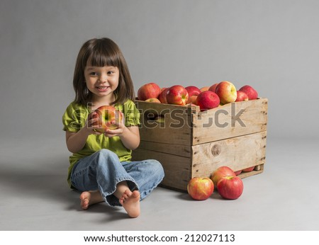 Child with crate of apples. - stock photo