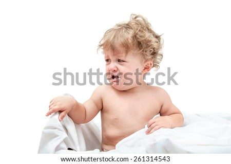 child with curly hair sitting at the table and crying isolated - stock photo