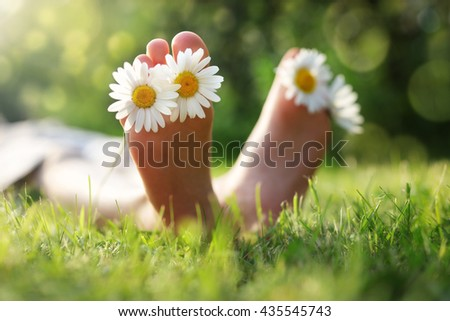 Child with daisy between toes lying in meadow relaxing in summer sunshine - stock photo