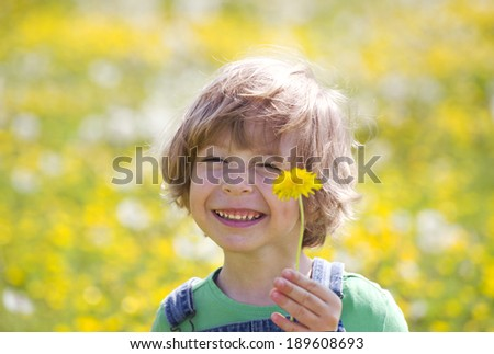 Child with dandelion on a yellow meadow - stock photo