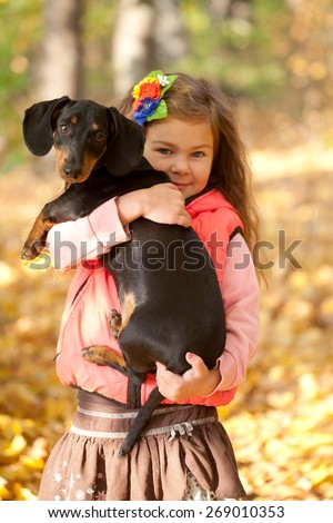 Child with dog. Little kid hugging dachshund puppy. Love to animals concept - stock photo