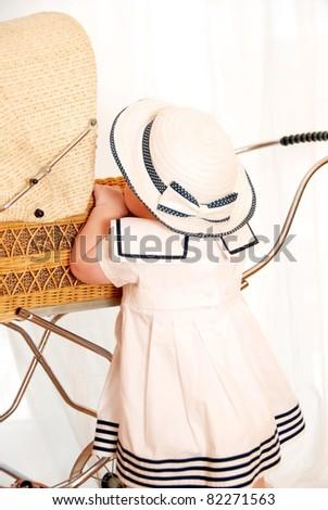 Child with doll's pram - stock photo
