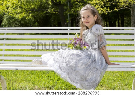 Child with flowers rests on a bench - stock photo