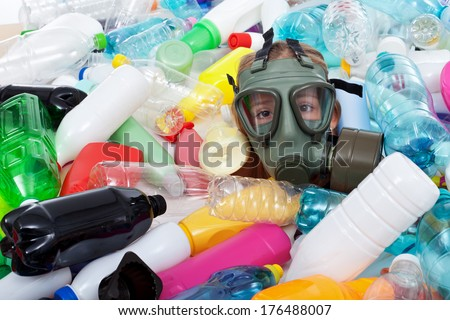 Child with gas mask covered with plastic bottles waste - stock photo