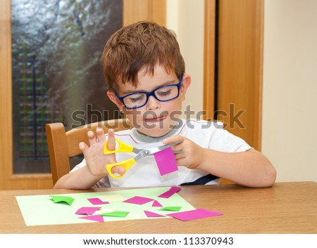 Child with glasses cutting paper with scissors - stock photo