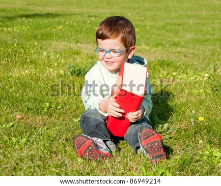 Child with glasses holding a red book sitting on grass - stock photo