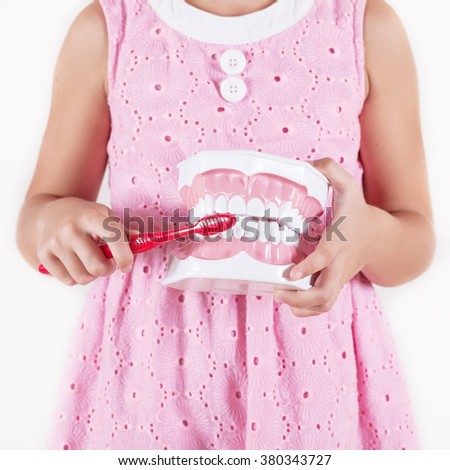 child with gloves showing on a jaw model how to clean the teeth with tooth brush properly and right - stock photo