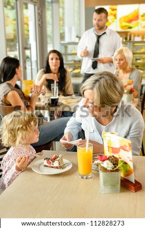 Child with grandmother at cafe eating cake sitting dessert restaurant - stock photo