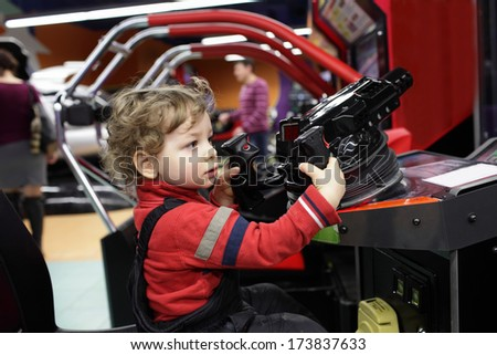 Child with gun at an amusement park - stock photo