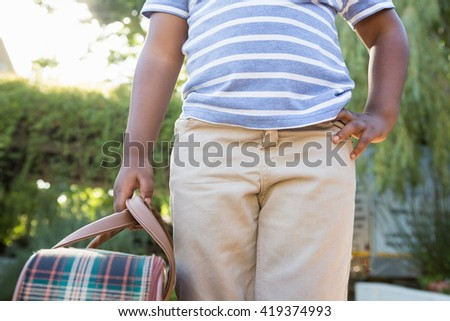 Child with hand on hips holding a bag in the park - stock photo