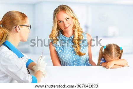 child with her mother on a visit at the doctor afraid vaccinations - stock photo