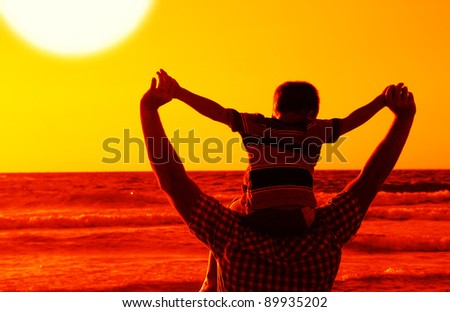 child with his father at sea on sunset - stock photo