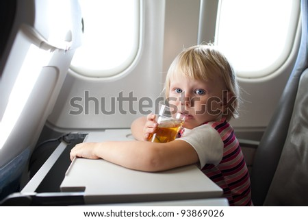 child with juice in airplane - stock photo