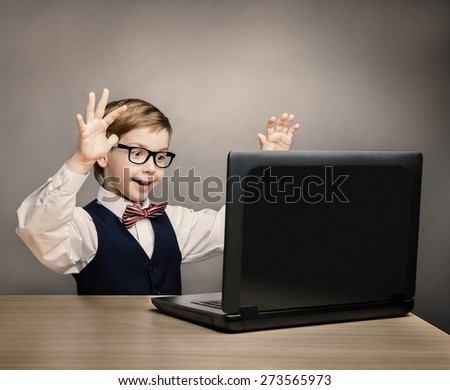 Child With Laptop, Little Boy in Glasses Happy Amazed Looking at Computer, School Kid Raised Hands over Gray Background, Internet Concept - stock photo