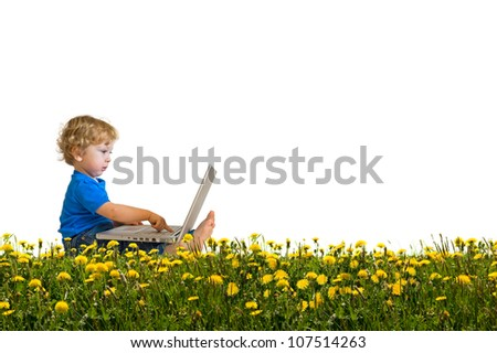Child with laptop on a dandelion meadow - stock photo