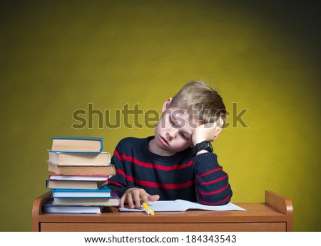 Child with learning difficulties. Tired boy doing home assignment. - stock photo