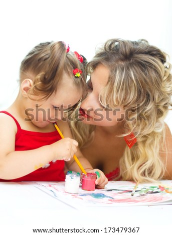 Child with mother painting indoors - stock photo