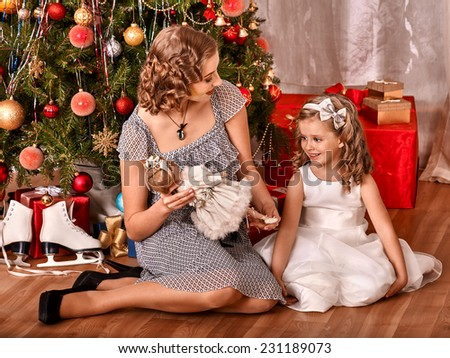 Child with mother receiving gifts under Christmas tree. - stock photo
