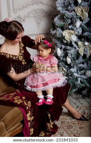Child with mother receiving near Christmas tree. Retro style. - stock photo