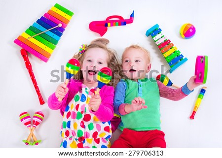 Child with music instruments. Musical education for kids. Colorful wooden art toys for kids. Little girl and boy play music. Kid with xylophone, guitar, flute. - stock photo