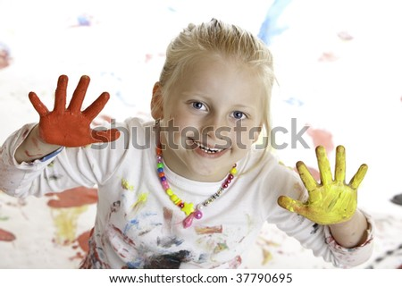 Child with painted hands smiles happy into camera. - stock photo