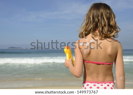 Child with painted sun made of sunscreen on back - stock photo