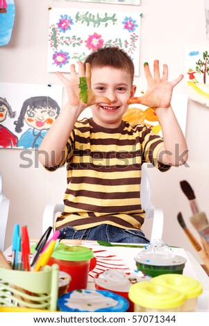 Child with picture and brush in play room. Preschool. - stock photo