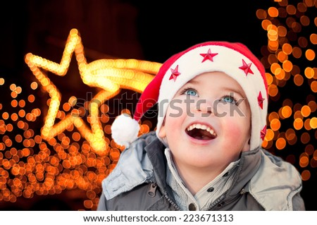 Child with Santa Claus hat looking at Christmas lights - stock photo