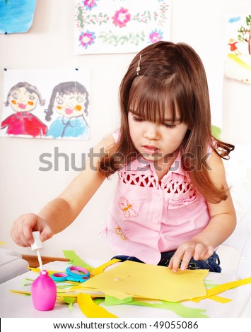 Child with scissors cut paper in play room. Preschool. - stock photo