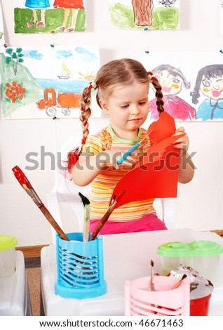 Child with scissors cut  paper  in playroom. Preschool. - stock photo