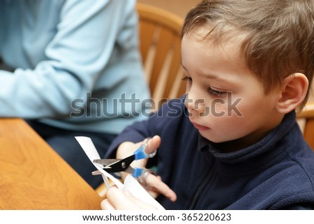 Child with scissors making paper snowflakes at workshop - stock photo