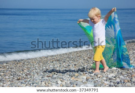 child with shawl goes on pebble beach - stock photo