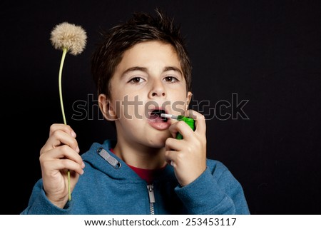 child with spray and dandelion -allergy - stock photo