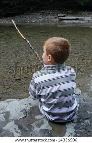 Child with stick enjoying a stream - stock photo