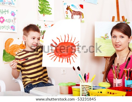 Child with teacher draw paint in play room. Preschool. - stock photo