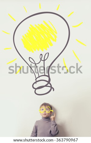 child with the light bulb. the concept of the idea - stock photo