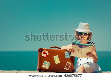 Child with vintage suitcase and city map on summer vacation. Travel and adventure concept - stock photo