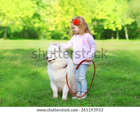 Child with white Samoyed dog on the grass in sunny summer day - stock photo