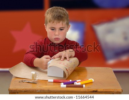 Child wrapping gift at school desk - stock photo
