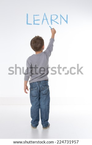 child writes the word �¢??learn�¢?� on a white wall - stock photo