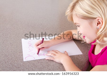 Child writing letter to Santa Claus, sitting at table - stock photo