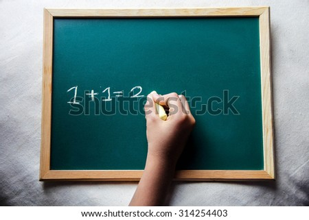 Child writing on wooden board in school. This photo may use as educational background. - stock photo