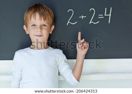 child writing sum on blackboard - stock photo