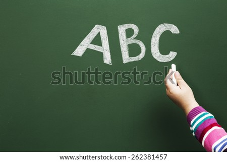 Child writting abd letters on green blackboard education concept - stock photo